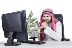 Arabian businessman with money on his computer. Picture of Arabian businessman feeling worried with money out of his computer, isolated on white background Royalty Free Stock Photo