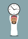 Arabian businessman with office clock above head. Time management or time is money business concept. Smiling cartoon arabian businessman holding office clock Royalty Free Stock Photos