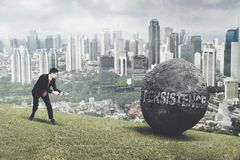 Arabian businessman pulling persistence word in hill. Arabian businessman struggling to pull a stone with persistence word while climbing on the hill Royalty Free Stock Image