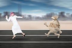 Arabian businessman running with Trump Effect word Stock Image
