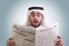 Arabian businessman shocked while reading newspape Stock Photo