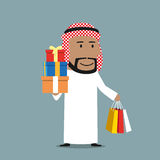 Arabian businessman with shopping bags and gifts. Cheerful smiling cartoon arabian businessman holding in hands colorful paper shopping bags and stack of gift Royalty Free Stock Photo