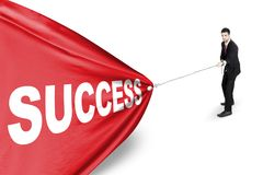 Arabian businessman pull success word on studio. Arabian businessman struggling to pull a banner with success word, isolated on white background Royalty Free Stock Images