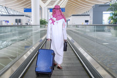 Arabian businessman with suitcases on the escalator Royalty Free Stock Photography