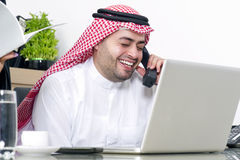 Arabian Businessman using Laptop and talking on phone Royalty Free Stock Photography