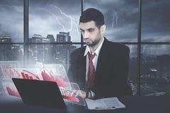 Arabian businessman with virtual declining graph. Picture of Arabian businessman looks sad while using a laptop with virtual declining finance graph Royalty Free Stock Photo
