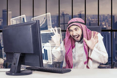 Arabian businessman with a virtual graph on computer Stock Images