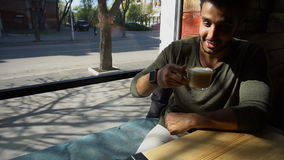 Arabian businessman waiting for partner and drinking coffee in slow motion. Handsome man sits near window and drinks coffee. Guy has short hair, beard and wears stock video footage