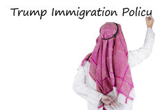 Arabian businessman writes Trump Immigration Policy word. Rear view of Arabian businessman writing Trump Immigration Policy word with a marker on the whiteboard stock photography