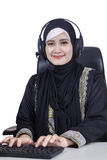 Arabian businesswoman with headphones. Portrait of middle eastern businesswoman typing on the keyboard while wearing headphones and islamic clothes stock photo