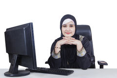 Arabian businesswoman imagines something on studio. Arabian businesswoman working with a computer on the table and looks imagines something, isolated on white royalty free stock photo