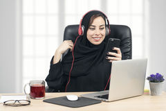 Arabian Businesswoman listening to music in the office Stock Image