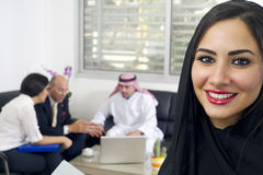 Arabian Businesswoman in office with Businesspeople meeting in the background Stock Photography