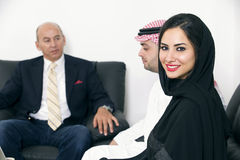 Arabian Businesswoman in office with Businesspeople meeting in the background Stock Image