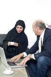 Arabian Businesswoman in office with Businesspeople meeting in the backgroundSenior Businessman working with Arabian Businesswoman Stock Image