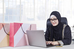 Arabian businesswoman shopping online in office. Beautiful Arabian businesswoman wearing islamic clothes and shopping online with laptop in the office Stock Photo