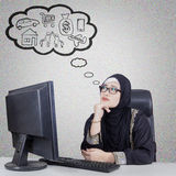 Arabian businesswoman thinking her dream. Beautiful Arabian businesswoman thinking her dream while sitting and daydreaming in front of computer Royalty Free Stock Photography