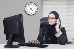 Arabian businesswoman working in the office. Beautiful Arabian businesswoman working in the office with computer while talking on the phone Royalty Free Stock Images
