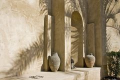 Arabian Corner. Arabian arch in shadow of palm tree with old arabic pottery Stock Photos
