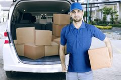 Arabian courier holding a clipboard and cardboard. Arabian male courier holding a clipboard and cardboard while standing near his van. Shot outdoors Stock Images