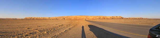 Arabian desert panorama. A wide-angle view stitched panorama of the desert in Saudi Arabia in the Al-Ghat valley during sunset; the shadow of the photographer Royalty Free Stock Photography