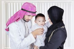 Arabian doctor examining a little boy. Portrait of Arabian doctor using stethoscope for examining a little boy while standing in the hospital stock photo