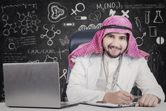 Arabian doctor with laptop and doodles. Male Arabian doctor smiling at the camera while working with laptop and clipboard on the table Stock Image