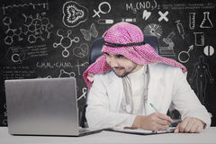 Arabian doctor looking at laptop in laboratory. Photo of Arabian doctor working in the laboratory while looking at the laptop screen with doodles on the Stock Photography