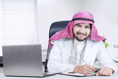 Arabian doctor working in the clinic. Portrait of Arabian doctor working in the clinic room with clipboard and laptop on the table, smiling at the camera Stock Photo