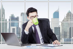 Arabian employee drinking coffee in the office. Portrait of a young Arabian businessman working in the office while enjoying a cup of coffee with a laptop on Royalty Free Stock Photography