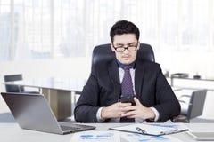 Arabian entrepreneur reading a message Stock Photography
