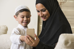 Arabian family, Arabian mother and son using mobile phone Stock Photo