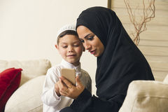 Arabian family, Arabian mother and son using mobile phone.  Royalty Free Stock Photo