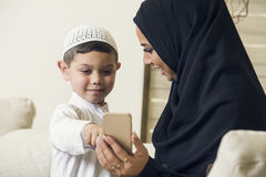 Arabian family, Arabian mother and son using mobile phone Stock Photos