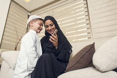 Arabian family, Arabian mother and son using mobile phone Royalty Free Stock Images