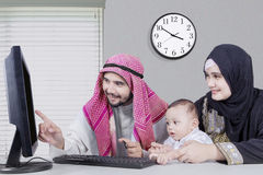 Arabian family buying something in online shop. Portrait of happy middle eastern family sitting and using computer for shopping online while holding credit card royalty free stock photos