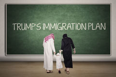 Arabian family with chalkboard in classroom. Arabian family walking into the classroom with Trump`s Immigration Plan word on the chalkboard Stock Photos