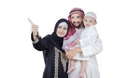 Arabian family look at something in studio Stock Image