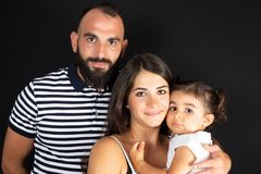 Arabian family portrait in studio black background father mother and son posing together royalty free stock photos