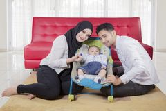 Arabian family posing in front of sofa. Happy family of father, mother, and baby boy posing in front of sofa royalty free stock photography