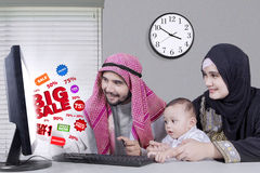 Arabian family shopping online in the office. Happy middle eastern family using computer for shopping online with big sale and discount while looking at the royalty free stock photography
