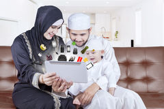 Arabian family shopping online with tablet. Portrait of middle eastern family sitting on the sofa while shopping online with tablet at home royalty free stock image