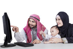 Arabian family using a computer. And looking at computer screen, isolated on white background royalty free stock photos