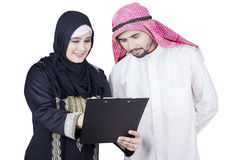 Arabian female worker and partner look at clipboard stock image