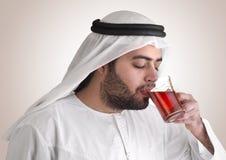 Arabian guy drinking tea / aroma tempting beverage royalty free stock photography
