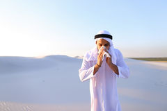 Arabian guy feels unpleasant sensations with cold, standing in m. Sad handsome young man, sheikh ill with cold and feels unwell, eases breathing with Stock Photo