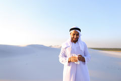 Arabian guy feels unpleasant sensations with cold, standing in m. Sad handsome young man, sheikh ill with cold and feels unwell, eases breathing with Royalty Free Stock Photography
