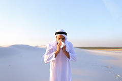 Arabian guy feels unpleasant sensations with cold, standing in m. Sad handsome young man, sheikh ill with cold and feels unwell, eases breathing with Royalty Free Stock Image