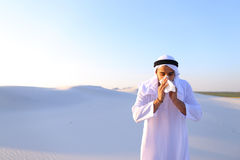 Arabian guy feels unpleasant sensations with cold, standing in m. Sad handsome young man, sheikh ill with cold and feels unwell, eases breathing with Stock Photos