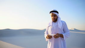 Arabian guy feels unpleasant sensations with cold, standing in middle of sandy desert on hot evening. Sad handsome young man, sheikh ill with cold and feels stock video